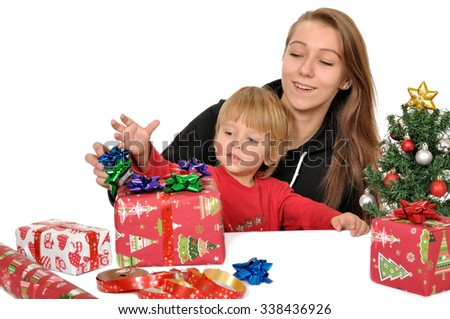3 year old boy and his sister and old sister is preparing christmas gifts on a