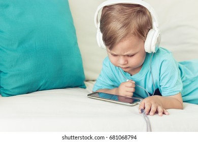 3 year old boy sits on the couch and listens to music. Little cute boy watching cartoons on the phone. Little boy.