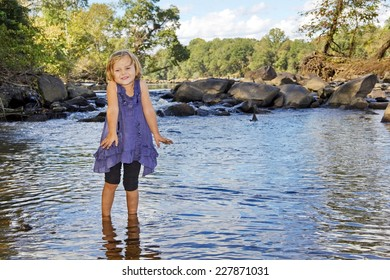 A 3 year old girl with muddy fingers and grin from playing, does the cold shrug shudder after wading in to the cold Catawba River,  near a small waterfall along the Riverwalk trail, Rock Hill, SC.