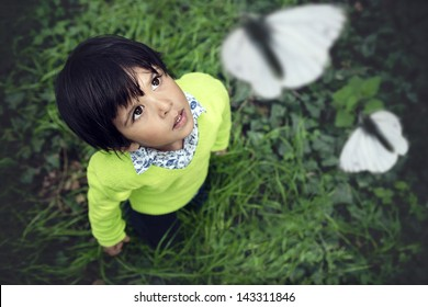 3 year old toddler looking up at white butterflies flying