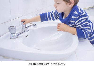3 years boy washing hands at adapted school sink. Learning hygiene habits