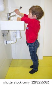 3 years child boy washing hands at adapted school sink but he reaches hardly to the faucet. Troubles on adapted washroom for children