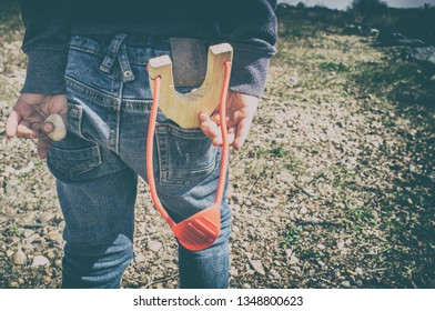 3 years little boy with slingshot in the jeans pocket. He is preparing next shot