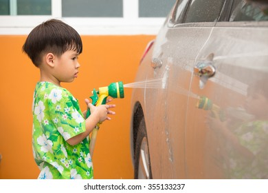 3 years old asian boy spraying water to wash a car
