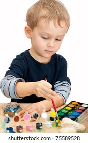 3 years old baby boy painting the stones with watercolor - over white background