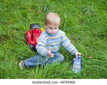3 years old boy playing toy truck in park