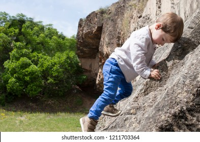 3 years old child boy climbing rock. Psychomotor development concept