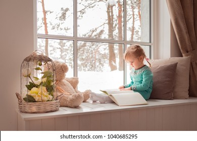 3 years old girl reading a book while sitting on window sill