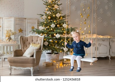 3 years old girl swinging on a wooden swing in a Christmas themed interior