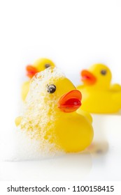 3 Yellow rubber ducks with soap suds on its head on white background