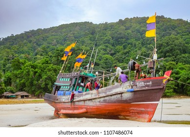 30 April 2018 - Myeik Archipelago, Myanmar. Fishermen cleaning fishing boat on beach of small island