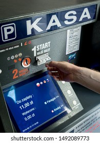 30 Aug 2019, Poznan, Poland. A man is paying his car parking using coin and collect the ticket at parking pay station terminal automatic machine.