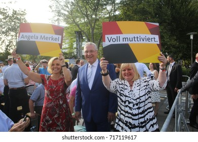 30 August, 2017  Erlangen , Germany Two CDU/CSU supporters hold placards aloft standing beside Joachim Herrmann, minister and CSU politician at an event during the German election campaign.