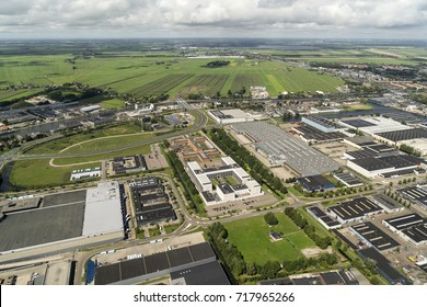 30 July 2017, Alphen aan den Rijn, Holland. Aerial view of prison, industrial area and a clear horizon with green fields, meadows and beautiful clouds.