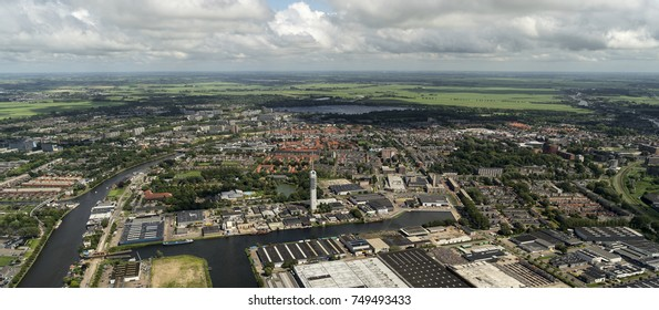 30 July 2017, Alphen aan den Rijn, Holland. Aerial view of a television transmission tower. On the clear horizon the city, green fields and a beautiful clear sky with cumulus clouds.