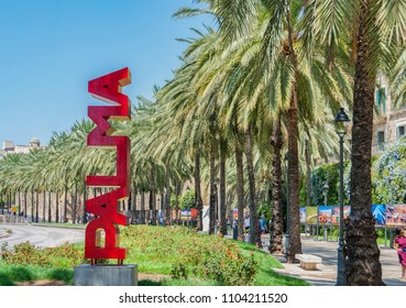 30 July 2017 - Palma de Majorca, Spain. Beautiful capital and the largest city of the Balearic islands. Red Palma sign and palma trees in the background.