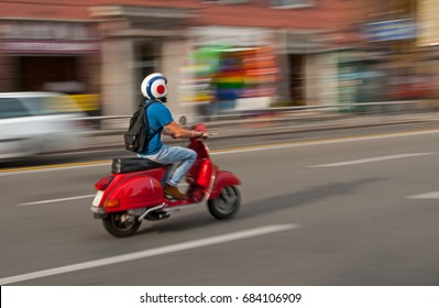 30 June 2017 - Genoa, Italy -  An unidentified man drives a traditional italian scooter - Vespa on the main street in Genoa