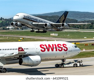 30 September 2016 Airbus A380 Singapore Airline, the biggest liner airplane, on takeoff and an Airbus A340 Swiss Air taxiing to gate at Zurich Kloten Airport, Switzerland. Zurich 30/09/2016