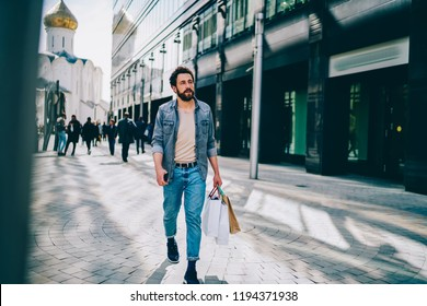 30 years old young man with paper bags in hands walking on shopping street and looking for branded shop with big sales for customers in Black Friday. Stylish male buyer with packages enjoying leisure