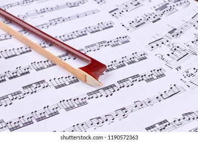 30.08.2017 - Kyiv, Ukraine. Brown violin bow on musical notes sheets. Fiddle stick on musical notes close up. Classical music background.