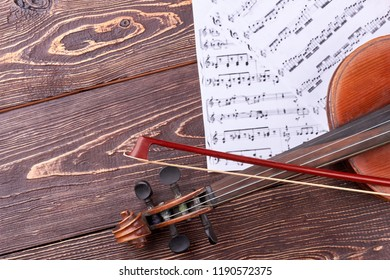 30.08.2017 - Kyiv, Ukraine. Violin, fiddle stick and musical notes. Old violin on textured wooden background, cropped image. Detail of violin.