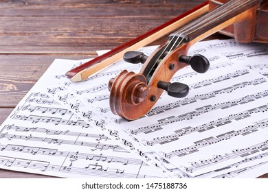 30.08.2017 - Kyiv, Ukraine. Violin scroll and peg box on musical notes. Music note sheets, violin and fiddle stick on wooden background. Detail of violin. Classical music concept.
