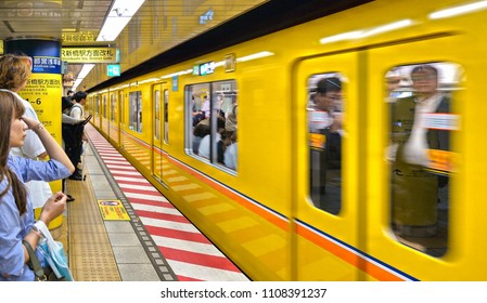 30.08.2017. subway station with yellow train and modern architecture with people waiting for train stop in Tokyo metro, Japan
