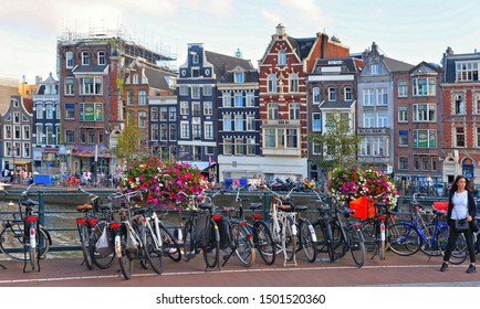 30.08.2019. Bike over canal Amsterdam city. Picturesque town landscape with people and old buildings facade in Netherlands with view on river Amstel.