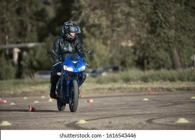 30-09-2019 Riga, Latvia Girl biker rides a motorcycle on the asphalt platform