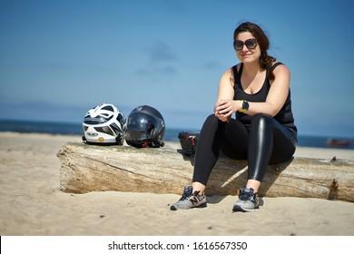30-09-2019 Riga, Latvia A girl on the beach sits on a log