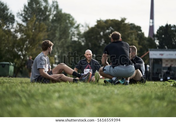 30-09-2019 Riga, Latvia A group of mens sit on green grass. Mens sitting on green grass