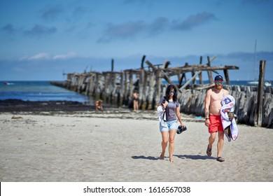 30-09-2019 Riga, Latvia A man and a woman walk along the beach near the pier