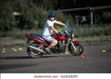 30-09-2019 Riga, Latvia Motorcyclist in white T-shirt and shorts rides a red motorcycle