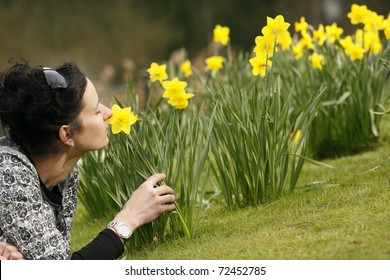 30-35 young happy woman sniffing daffodil lying on grass in public park