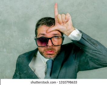 30s or 40s messy businessman in suit and tie sad and ashamed in weird broken nerdy glasses doing loser sign with hand and fingers on his forehead with funny expression in unsuccessful concept