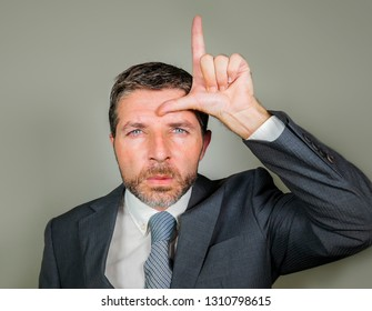 30s or 40s unshaven sad and ashamed businessman crying doing loser sign with hand and fingers on his forehead with funny depressed expression in unsuccessful career concept