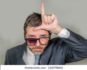 30s or 40s unshaven sad and ashamed businessman in weird broken glasses doing L loser sign with hand and fingers on forehead with funny depressed expression in unsuccessful concept