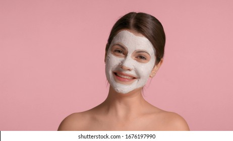 30s brunette woman with a facial clay mask on laughing and having fun making faces in studio on pink background