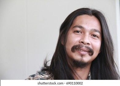30s Thai man in his chilling time.Thai man looking to camera with a little smile on his face.Dark tan and traditional Thai characteristic,charming with long black hair,mustache and beard.Ethnic Thais.