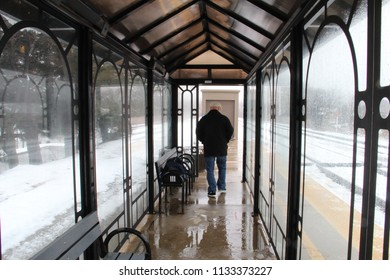 A 30-something man in a black fitted jacket and beige driving cap paces with back to camera and hands in pockets while waiting in a train station vestibule with walls of arched glass and a-frame roof.