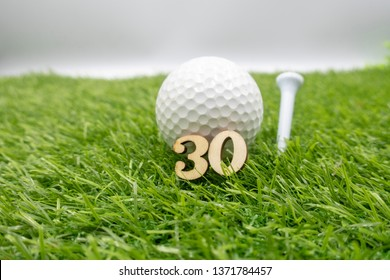30th birthday golfer with number 30 and golf ball with colourful tees on green