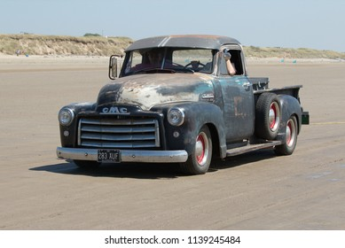 30th June 2018- A 1952 American GMC 100 pickup truck being driven at a hot rod event on the sandy beach at Pendine, Carmarthenshire, Wales, UK.