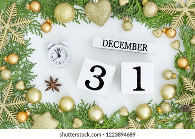 31 december perpetual calendar and alarm clock 12 hours. Happy new year greeting card design Green frame made of Christmas trees and golden decorations,ball,snowflakes,anise. Greeting card design.