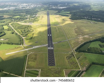 31 July 2017, Enschede, Holland. Aerial view  of Twente Airport, a former military Dutch airforce base. The black runway is surrounded by green grass. A cloud shade is over the field.