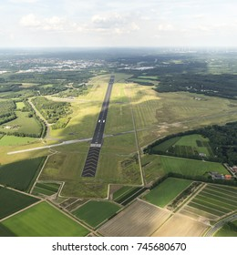 31 July 2017, Enschede, Holland. Aerial view  of Twente Airport, a former military Dutch airforce base. The black runway is surrounded by green grass. A cloud shade is over the field. A clear horizon.
