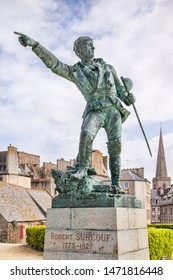 31 March 2015:  Saint-Malo, Brittany, France - Statue of Robert Surcouf, a famous privateer of St Malo with the town in the background.