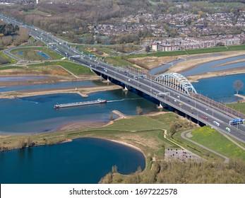 31 March 2020, Vianen, Holand. Aerial view of bridge Lekbrug and Jan Blankenbrug over river Lek near Nieuwegein. Highway A2 has 10 lanes. A freight ship has just passed the bridge.