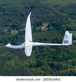31 May 2021, Veluwe, Holland. Aerial view air-to-air of glider Schleicher ASG 29E, registration PH-1650 in mid air. Pilot flying the white sailplane is smiling Lars Groot.