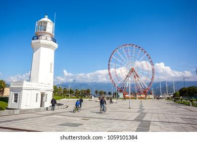 31.03.2018 Batumi, Georgia - Ferris wheel and Batumi lighthouse on the Batumi Seafront Promenade in the sunny day, Adjara.