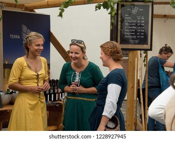 31.8.2018, Trnava, Slovakia Three young women in historical clothing are talking at the table with wine.The image is from the traditional medieval crushing grapes, which takes place in the court.